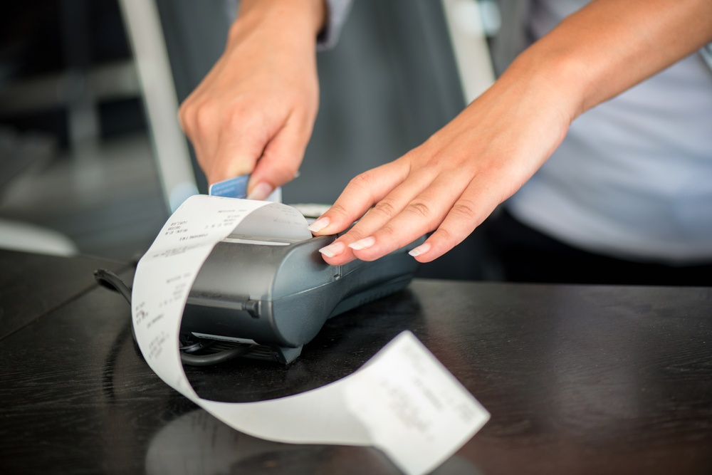 Hands operating pos terminal with magnetic card.jpeg